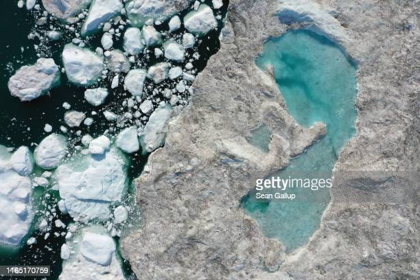 In this aerial view melting ice forms a lake on free-floating ice jammed into the Ilulissat Icefjord during unseasonably warm weather on July 30,...