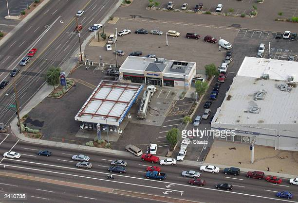 In this aerial view motorists line up in a circular pattern at top and down the street at lower right after following a tanker truck into a gas...