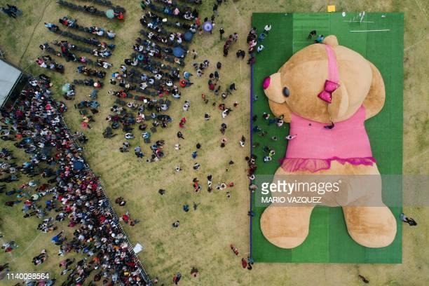 In this aerial view officials measure a giant teddy bear measuring more than 20 metres long and weighing four tons which entered the Guinness Book of...