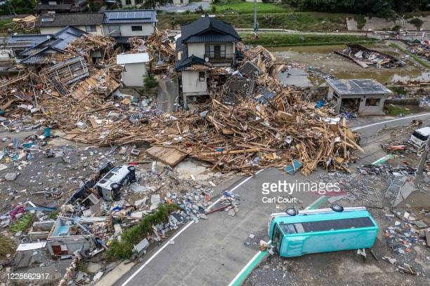 In this aerial view, overturned vehicles lie next to a ruined house that is surrounded by debris and driftwood after the nearby Kuma River flooded...