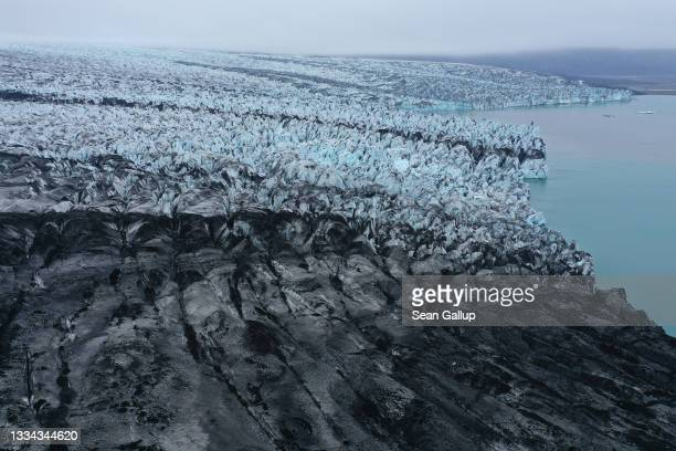 In this aerial view receding Breidamerkurjokull glacier, a portion of it black with volcanic dust and stones, ends at Jokulsarlon lake on August 15,...