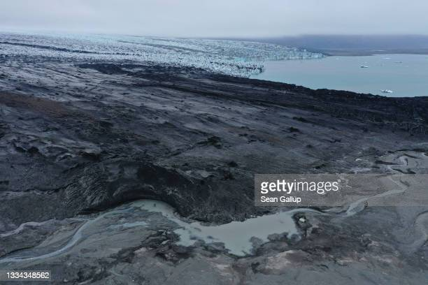 In this aerial view receding Breidamerkurjokull glacier, a portion of it black with volcanic dust and stones, ends at Jokulsarlon lake and creates a...