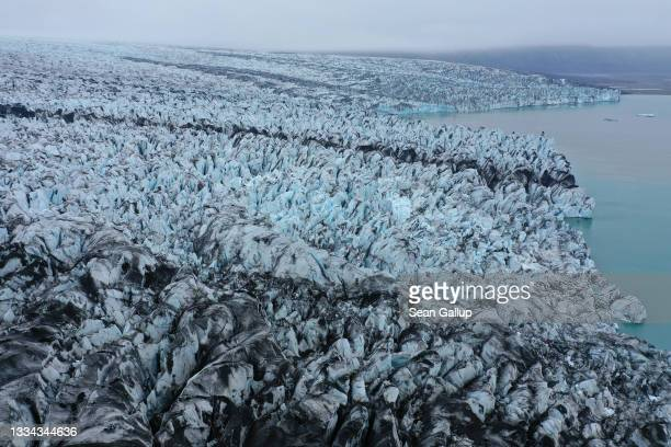 In this aerial view receding Breidamerkurjokull glacier, portions of it black with volcanic sand and stones, ends at Jokulsarlon lake on August 15,...