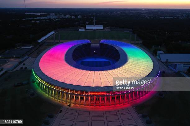 In this aerial view the Olympiastadion stadium stands illuminated in LGBT rainbow colors on June 23, 2021 in Berlin, Germany. Stadiums and landmarks...