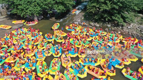 In this aerial view tourists ride in inflatable boats as they go rafting down a river at Yao Mountain Scenic Spot on August 8 2020 in Pingdingshan...