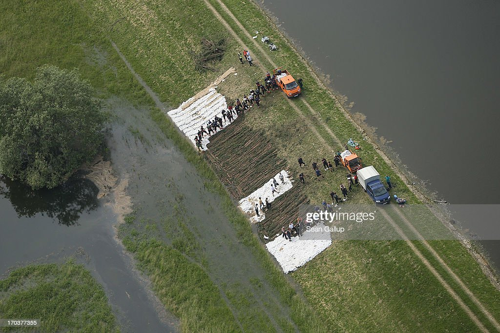In this aerial view volunteers and firemen stack sandbags to strengthen a dyke at the flooding Elbe river on June 12, 2013 near Wittenberge, Germany. The swollen Elbe is continuing to danger communities along its northern route in Saxony-Anhalt and Brandenburg states, though the bursting of a dyke near Fischbeck has relieved some pressure from towns farther north. Floods have ravaged portions of southern and eastern Germany in the last week, leaving at least eight people dead and forcing tens of thousands to evacuate their homes.
