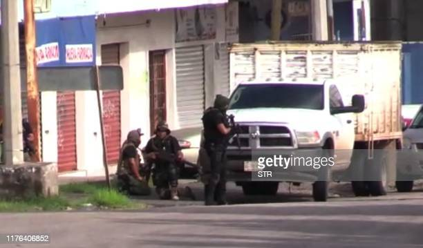 In this AFPTV screen grab armed gunmen take position in a street of Culiacan state of Sinaloa Mexico on October 17 2019 Heavily armed gunmen in...