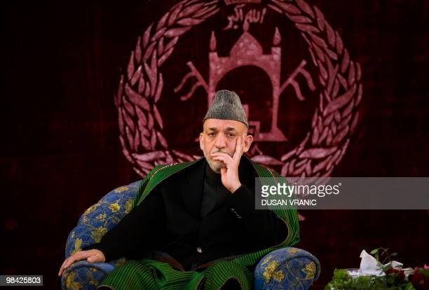 In this April 11, 2010 photograph, Afghan President Hamid Karzai listens to local elders in Kunduz, Afghanistan. Karzai urged Taliban insurgents to...