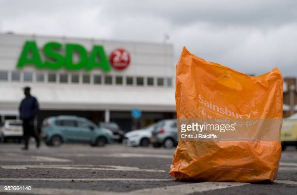 In this arranged photo illustration a Sainsbury's shopping bag is seen on the ground in the car park of an Asda supermarket on April 29 2018 in...