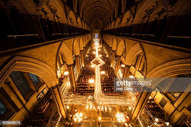 In this combination of two images the interior of Salisbury Cathedral is illuminated by trails of candles carried by choristers during the annual...