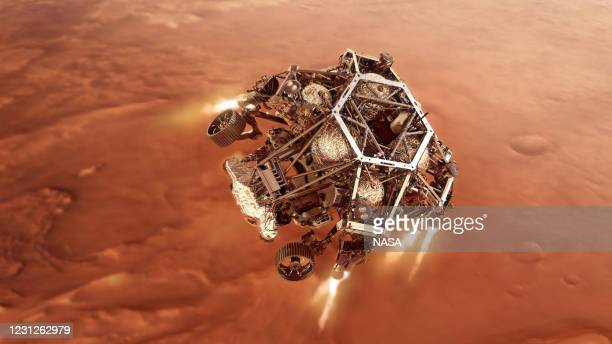 In this concept illustraion provided by NASA, NASA's Perseverance rover fires up its descent stage engines as it nears the Martian surface to land in...