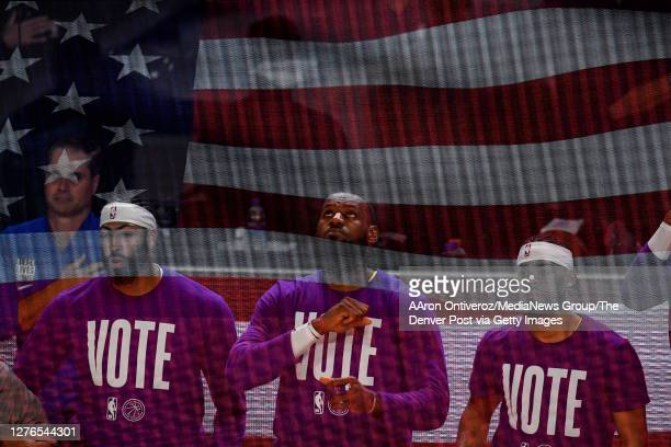 In this double exposure LeBron James of the Los Angeles Lakers is joined by teammates Anthony Davis and Quinn Cook as they kneel during the national...