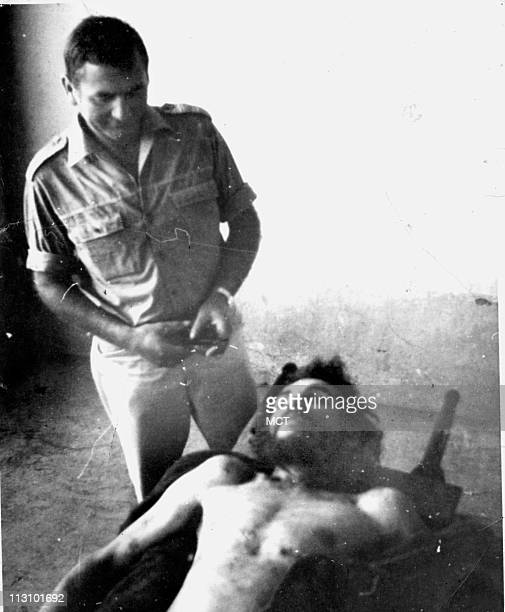 In this Erich Blossl photo an unidentified man stands over the body of Che Guevara who was executed in 1967 in La Higuera Bolivia