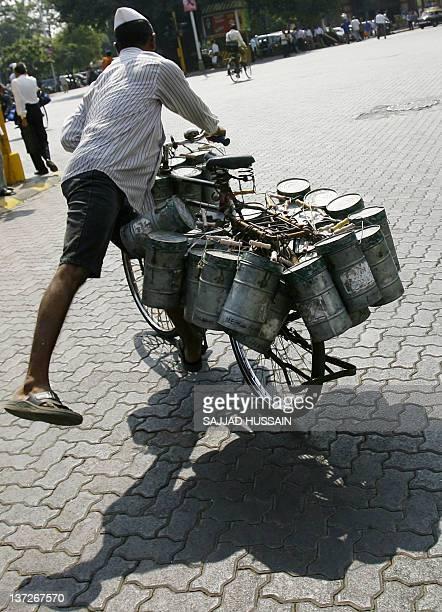 STORY 'LIFESTYLEINDIAHEALTHFOODOBESITYBUSINESS' In this file photgraph taken on Novemer 15 2007 a Mumbai dabbawalla or lunchbox deliveryman mounts...