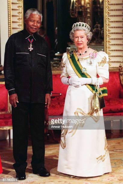 In this file photo Queen Elizabeth II poses with Nelson Mandela at Buckingham Palace on May 3 2000 in Windsor England