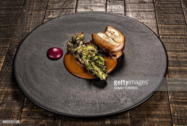 In this file photo taken on April 05 a dish called Lechon Confitado with Xanducata and purple carrot is pictured at Mexican chef Fernando Martinez's...