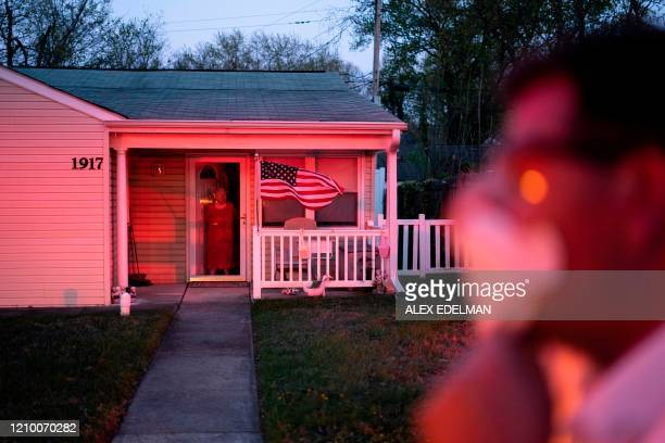 In this file photo taken on April 10 a bystander looks on as firefighters and paramedics with Anne Arundel County Fire Department respond to an alarm...