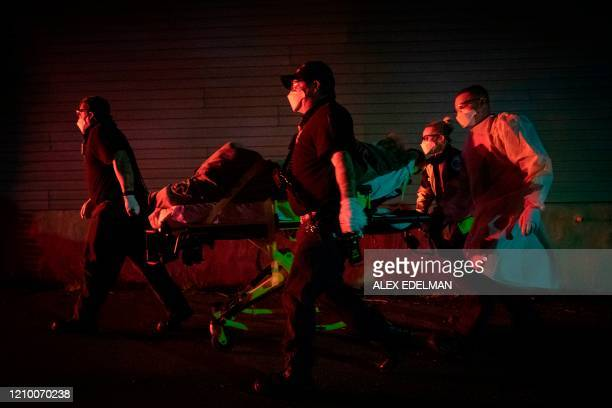 In this file photo taken on April 13 firefighters and paramedics with Anne Arundel County Fire Department transport a patient on a stretcher in Glen...