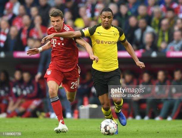 In this file photo taken on April 6 2019 Bayern Munich's striker Thomas Mueller and Dortmund's French defender Abdou Diallo vie for the ball during...