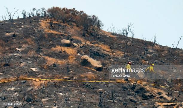 In this file photo taken on August 10 2018 Firefighters walk through the burned area at the Holy Fire in Lake Elsinore California southeast of Los...