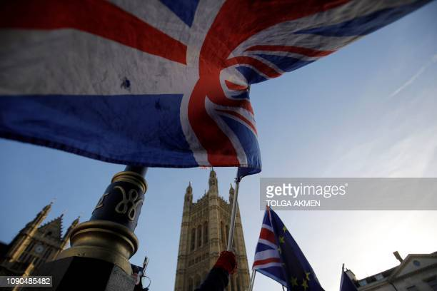 In this file photo taken on December 17, 2018 Anti-brexit campaigners wave Union and EU flags outside the Houses of Parliament in central London. -...