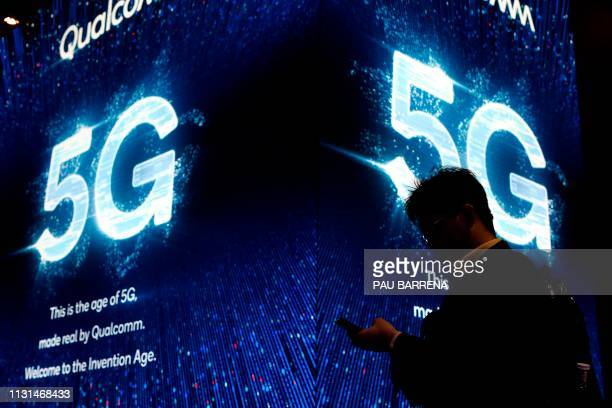 In this file photo taken on February 27 2019 a man uses his phone next to a 5G sign at the Qualcomm stand at the Mobile World Congress in Barcelona...