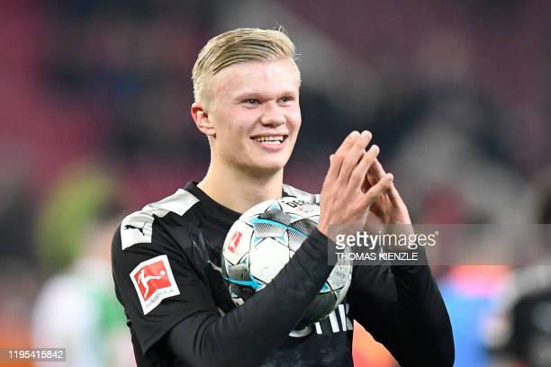 In this file photo taken on January 18, 2020 Dortmund's Norwegian forward Erling Braut Haaland smiles as he holds the match ball after his team's 5-3...