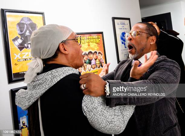 In this file photo taken on January 19 2019 Melvin Glover aka Melle Mel hugs Guy O'Brien aka Master Gee from the Sugarhill gang at the HipHop Museum...