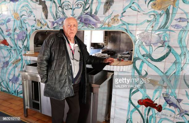 In this file photo taken on January 31 2018 Gilles Esmiol poses in front of a fresco painted by French sculptor Jean Marais and listed as a...