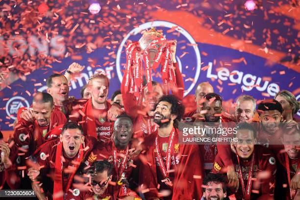 In this file photo taken on July 22, 2020 Liverpool's English midfielder Jordan Henderson lifts the Premier League trophy during the presentation...