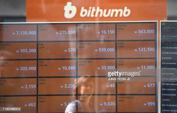 In this file photo taken on June 20 2018 a woman is reflected on a screen showing exchange rates of cryptocurrencies at Bithumb virtual currency...