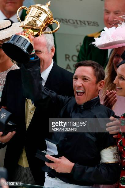 In this file photo taken on June 20 Italian jockey Frankie Dettori raises the Gold Cup during the presentation after he won the Gold Cup race on...