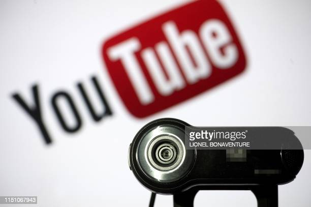 In this file photo taken on June 28, 2013 a webcam is positioned in front of YouTube's logo in Paris. - Millions of children regularly use YouTube to...