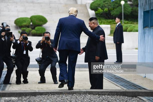 In this file photo taken on June 30 US President Donald Trump steps into the northern side of the Military Demarcation Line that divides North and...