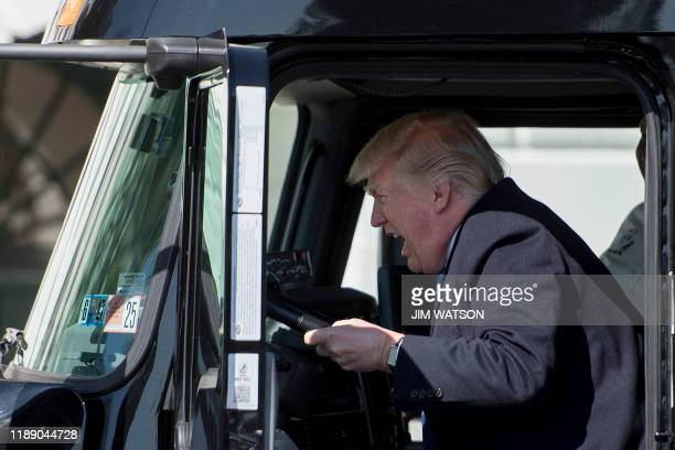 In this file photo taken on March 23 2017 US President Donald Trump sits in the drivers seat of a semitruck as he welcomes truckers and CEOs to the...