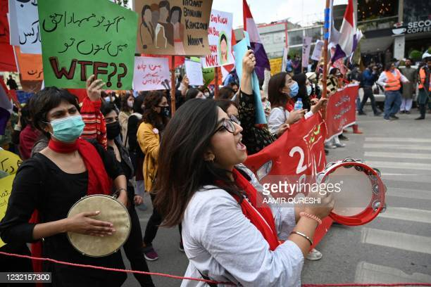 In this file photo taken on March 8, 2021 activists of the 'Aurat March' shout slogans and carry placards during a rally to mark International...
