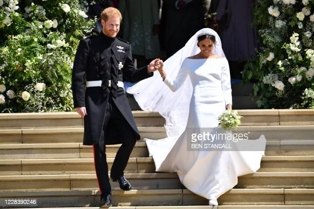 In this file photo taken on May 19 Britain's Prince Harry, Duke of Sussex and his wife Meghan, Duchess of Sussex emerge from the West Door of St...