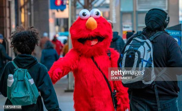 In this file photo taken on November 04 2019 A person dressed as Sesame Street character Elmo greets people on 42nd Street in New York Generations of...