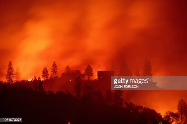 In this file photo taken on November 11 flames from the Camp fire burn near a home atop a ridge near Big Bend California With the embers still...