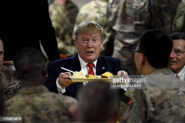 In this file photo taken on November 28, 2019 former US President Donald Trump serves Thanksgiving dinner to US troops at Bagram Air Field during a...