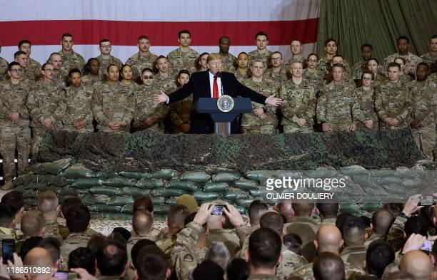 In this file photo taken on November 28 US President Donald Trump speaks to the troops during a surprise Thanksgiving day visit at Bagram Air Field...