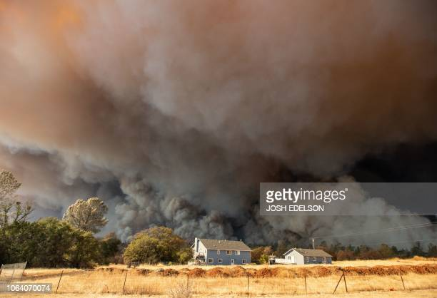 In this file photo taken on November 8 2018 a home is overshadowed by towering smoke plumes as the Camp fire races through town in Paradise...