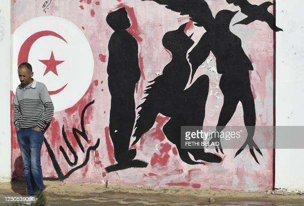 In this file photo taken on October 27, 2020 a man waits by a graffiti depicting silhouettes of a man metamorphosing into a bird symbolising freedom,...
