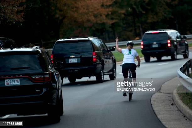 In this file photo taken on October 28 Juli Briskman shows her middle finger as a motorcade with US President Donald Trump departs Trump National...
