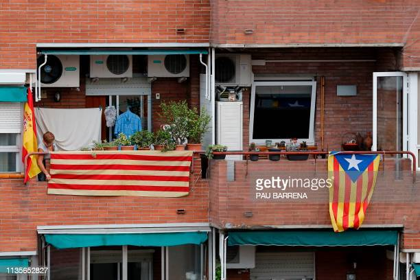 In this file photo taken on September 25, 2017 a woman hangs a Catalan flag next to a Spanish flag on her balcony, next to an Estelada hanging from a...