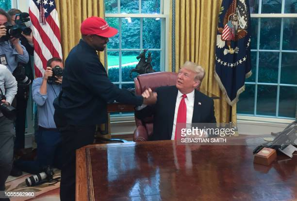 in this file photo US President Donald Trump meets with rapper Kanye West in the Oval Office of the White House in Washington DC October 11 2018...