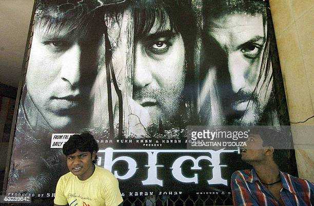 In this file photograph dated 29 April 2005 Indian cinema goers sit in front of a billboard advertising the film 'Kaal' outside a cinema hall in...