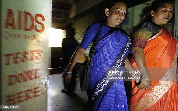 In this file picture taken 21 January 2005 two Indian sex workers walk handinhand past a sign for AIDS testing at a clinic in Bangalore India has the...