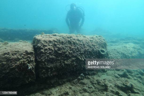 In this file taken on August 18 a dive guide shows tourists a archaeological find from the Roman era from Terme del Lacus,the submerged ancient Roman...