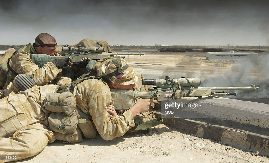 In this hand out image by the British Defence Ministry, (L-R) Lance Sergeant Chris Briggs and Guardsman Warren Bradford serve as a snipers with Support Company attached to Number 1 Company 1st Battalion The Irish Guards April 3, 2003 in Basra, Iraq. In a dawn raid on a university factory complex within sight of their patrol base at Bridge Four on the outskirts of Basra, the Irish Guards attacked and cleared the base after coming under fire from small arms mortars and SAM Missile systems, which were fired from Iraqi positions at a British Lynx Helicopter supporting the Irish Guards. Briggs and Bradford are one of four sniper pairs set up within the buildings to provide covering fire for the Royal Engineers attempting to put out one of the numerous oil well fires.
